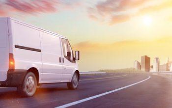 Van Lieferwagen mit Fracht macht einen Transport auf einer Straße zur Stadt